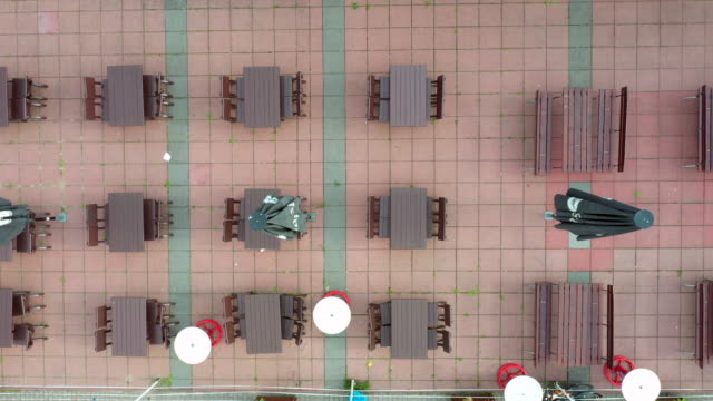 "vídeos y material grabado en eventos de stock de in this aerial view outdoor tables and chairs stand at a closed beer garden restaurant at the ""spinnerbruecke"" , a well-known place for bikers,... - mesa cenital"