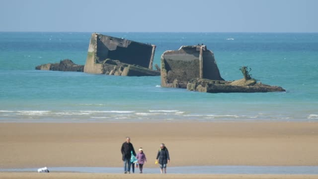 vídeos de stock, filmes e b-roll de in this aerial view pieces of the world war ii allied temporary mulberry harbor built during the dday invasion lie in the water at asnelles on april... - arromanches