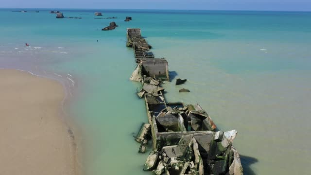 in this aerial view pieces of the world war ii allied temporary mulberry harbor built during the d-day invasion lie in the water at asnelles on april... - normandy stock videos & royalty-free footage