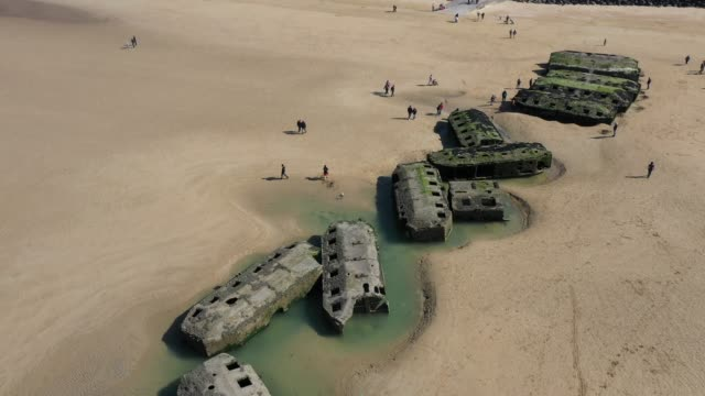In this aerial view pontoons from the World War II Allied temporary Mulberry harbor built during the DDay invasion lie on the beach on April 30 2019...