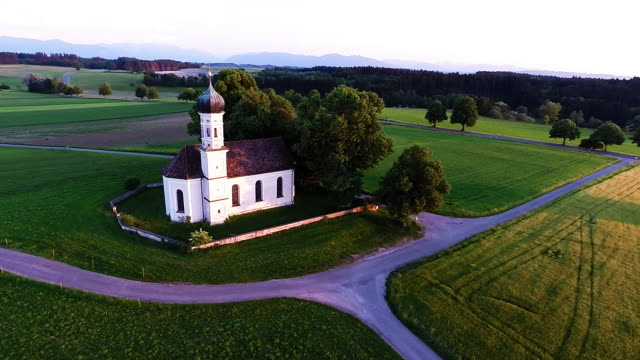 stockvideo's en b-roll-footage met in this aerial view stmarinus and anian church stands as the bavarian alps are visible behind on june 3 2015 at wilparting near irschenberg germany... - bavarian alps