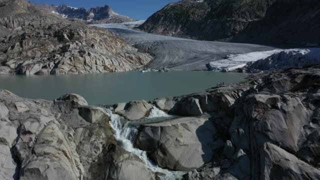 in this aerial view the rhone glacier lies behind a lake and waterfall formed by the glacier's meltwater on august 23, 2019 near obergoms,... - flowing water stock videos & royalty-free footage