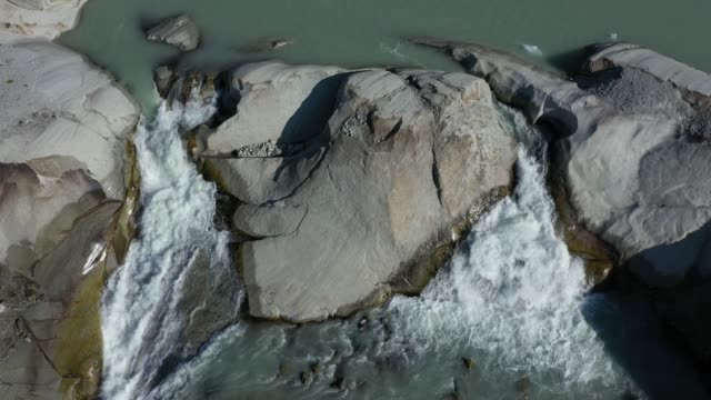 in this aerial view the rhone glacier water flows from a waterfall formed by the glacier's meltwater on august 23, 2019 near obergoms, switzerland.... - flowing water stock videos & royalty-free footage