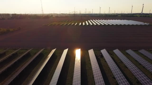 in this aerial view the sun sets over a field of solar energy panels as wind turbines spin nearby on september 4, 2015 near nauen, germany. germany... - physical activity stock videos & royalty-free footage