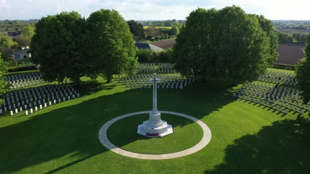 stockvideo's en b-roll-footage met in this aerial view the sun sets over graves at the commonwealth war graves commission's bayeux war cemetery on may 3 2019 at bayeux france the... - geallieerde mogendheden