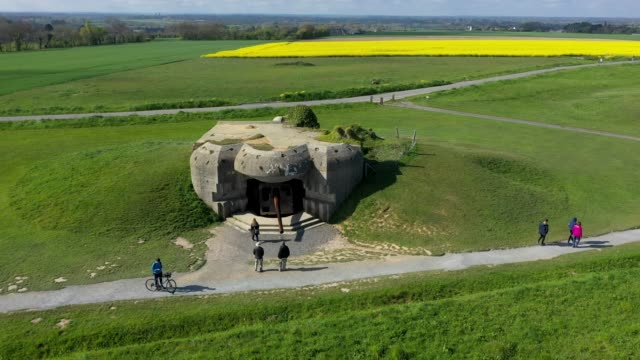 in this aerial view visitors walk among former german artillery bunkers that point towards the english channel on may 3 2019 at longuessurmer france... - normandie stock-videos und b-roll-filmmaterial