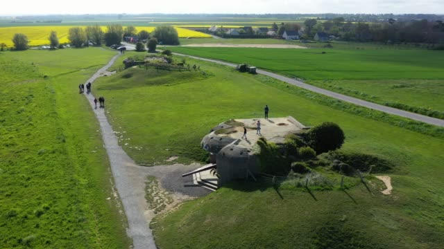 in this aerial view visitors walk among former german artillery bunkers that point towards the english channel on may 3 2019 at longuessurmer france... - d day stock-videos und b-roll-filmmaterial