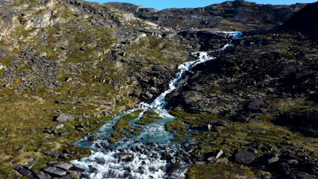 in this aerial view water from the greenland ice sheet rushes down at what a local guide said is an unprecedentedly high level in the last 19 years... - nature stock videos & royalty-free footage