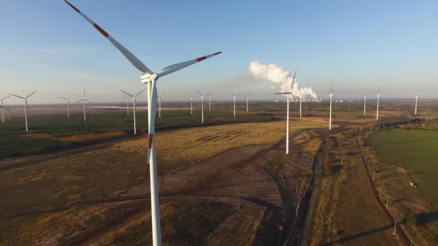 in this aerial view wind turbines spin as steam rises from the cooling towers of the jaenschwalde coal-fired power plant on november 15, 2018 near... - brandenburg state stock videos & royalty-free footage