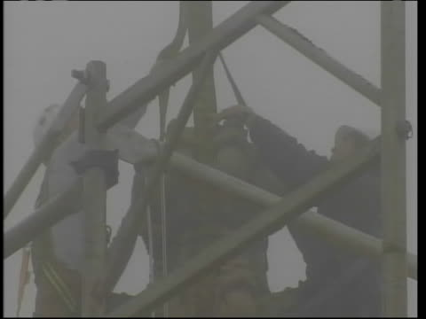 vídeos de stock e filmes b-roll de in this clip engineers are working in fog, preparing to remove parts of a pinnacle on the washington national cathedral after it was damaged by the... - 12 15 meses