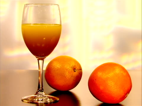 vídeos de stock e filmes b-roll de in this clip there is a wine glass half full of orange juice with two orange fruit oranges on table next to glass in early january of 2012 the us... - vitamina c