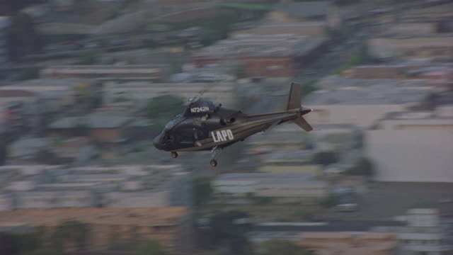 in this following daylight shot, an lapd helicopter flies over downtown los-angeles. - los angeles police department stock videos & royalty-free footage