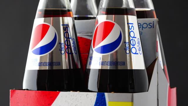 in this 'illustrative editorial' clip, bottles of pepsi cola carbonated drink turn on a display on february 15, 2015. pepsi cola drinks are produced... - editorial bildbanksvideor och videomaterial från bakom kulisserna