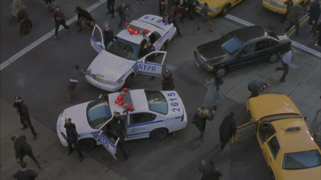 in this point-of-view shot from overhead, police officers aim and fire their guns at a target above them as pedestrians run through the parked cars in all directions. - crowd running scared stock videos & royalty-free footage