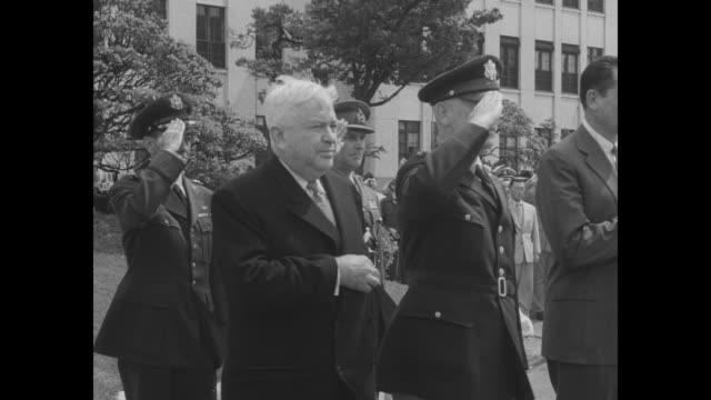 in tokyo us defense secretary charles wilson shakes hands with us military officers standing in reception line / honor guard holding flags stands at... - ellis briggs stock videos & royalty-free footage