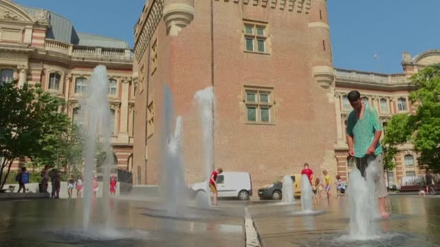 in toulouse children play in water jets while adults shelter from the sun under trees - toulouse stock videos & royalty-free footage