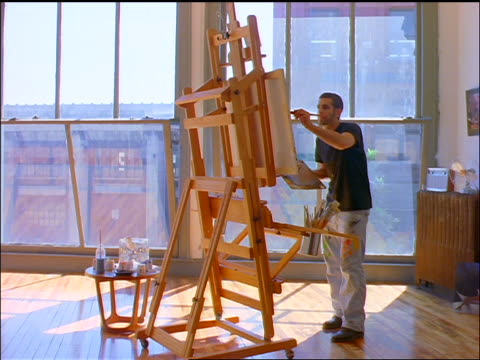 STEADICAM in towards Gen X man painting at easel by window in loft