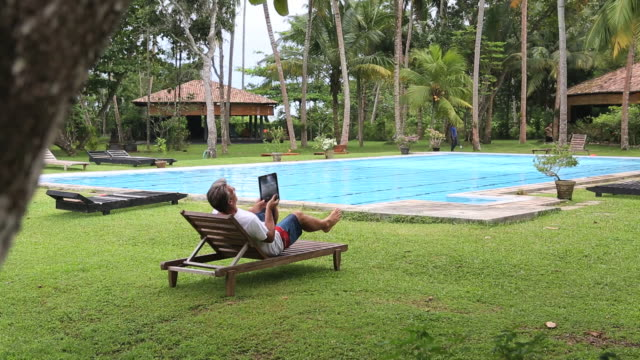 in tropics, man uses tablet while relaxing near pool - beach chairs stock videos & royalty-free footage