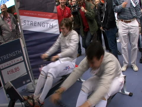 fencers in uniform doing rowing game at countdown to olympics event in times square in new york city - sport stock videos & royalty-free footage