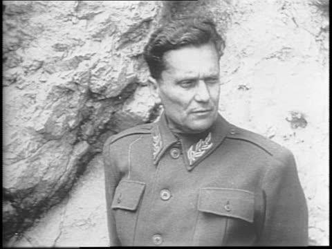 in yugoslavia partisans of marshal tito assemble in street / woman examines machine gun / men and women guerillas walk in line / tito accompanied by... - 旧ユーゴスラビア点の映像素材/bロール