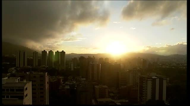 inauguration day support for absent hugo chavez; venezuela: caracas: ext sunrise over caracas hugo chavez supporters chanting chavez supporters zoom... - caracas stock videos & royalty-free footage