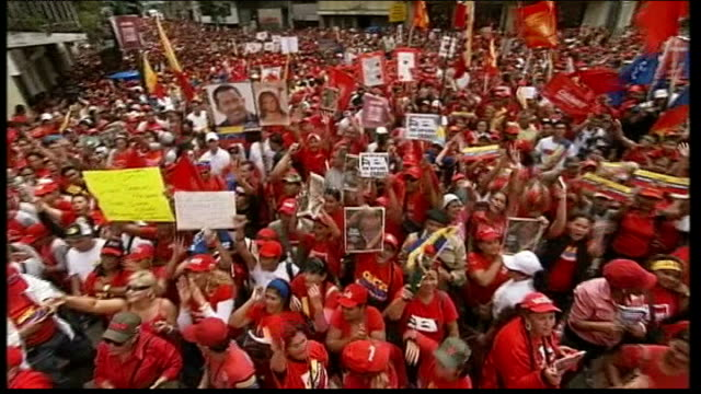inauguration day support for absent hugo chavez woman on stage singing pan demonstrators waving banners man holding up thumb chavez action doll - ウゴ・チャベス点の映像素材/bロール