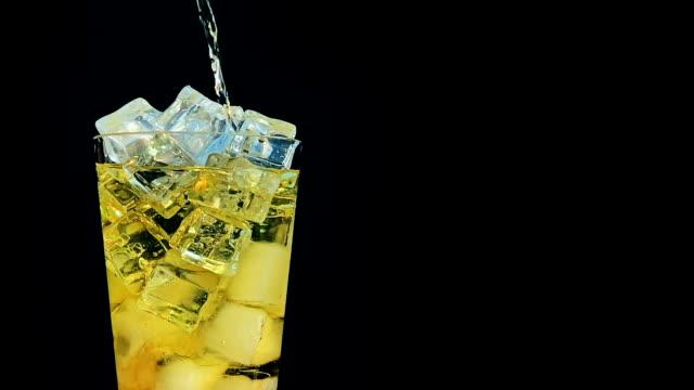 vidéos et rushes de verser la soude inka kola dans un verre de glace au ralenti sur fond noir - verre d'eau