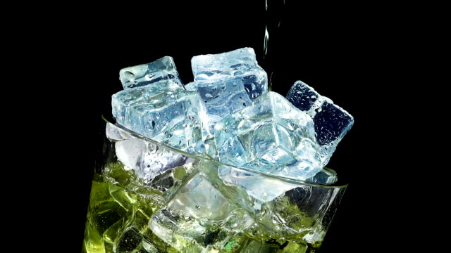 Pouring Inka Kola soda into a glass of ice at slow motion on a black background