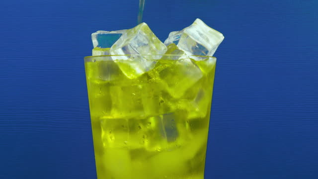 inca kola soda pouring into a glass of ice on a blue background. - carbonated stock videos & royalty-free footage