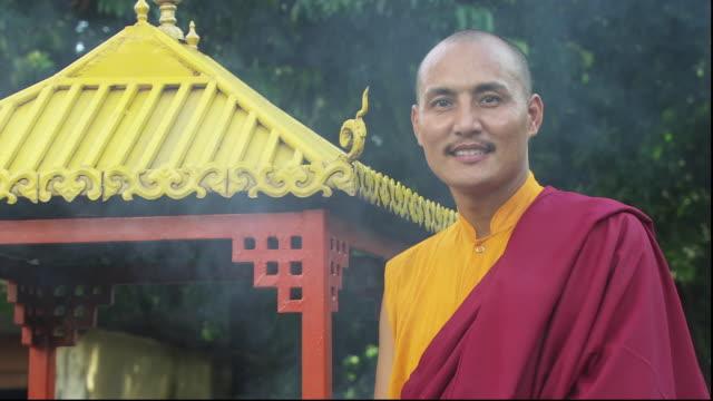 stockvideo's en b-roll-footage met incense billows behind a monk standing near a gazebo. available in hd. - gazebo