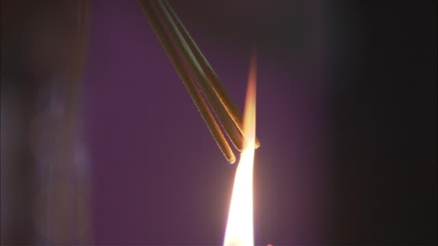 incense sticks are lit from a candle flame. - religion stock videos & royalty-free footage