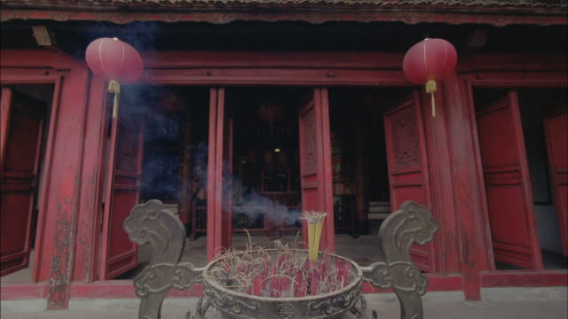 Incense sticks burn in front of a shrine.