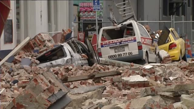 includes fallen bricks badly damaged vehicles emergency services and smoking remains of canterbury television building in which 115 people were killed - カンタベリー点の映像素材/bロール