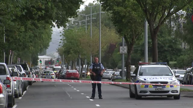 including armed police guarding tape cordon and bystanders and families starting to gather at scene of mass shootings in central christchurch - christchurch stock-videos und b-roll-filmmaterial