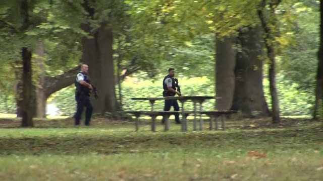 including armed police officers running through hagley park adjacent to masjid al noor mosque in wake of mass shootings in central christchurch. - terrorism stock videos & royalty-free footage