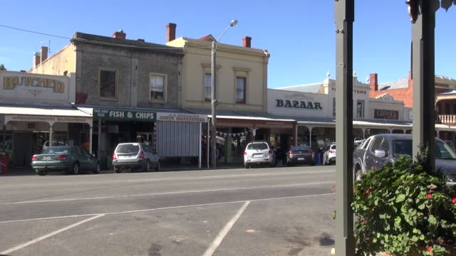 including fish and chip restaurant and butchers. plus woman crossing road talking on a mobile phone. beechworth saw major growth during the goldrush... - town stock videos & royalty-free footage