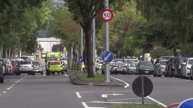 including police and ambulance vehicles with lights flashing and sirens sounding driving on streets nearby masjid al noor mosque in wake of mass... - christchurch stock-videos und b-roll-filmmaterial