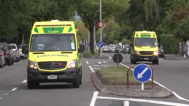 including police and ambulance vehicles with lights flashing and sirens sounding stationary and driving on streets nearby masjid al noor mosque in... - christchurch stock-videos und b-roll-filmmaterial