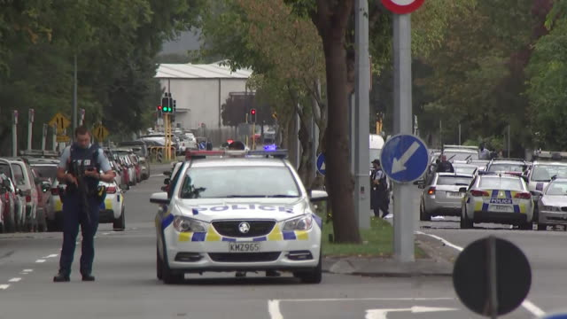 including police vehicles with lights flashing and sirens sounding driving around streets of central christchurch armed police guarding scene of mass... - christchurch stock-videos und b-roll-filmmaterial
