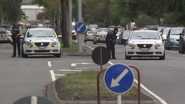 including police vehicles with lights flashing and sirens sounding driving around streets of central christchurch armed police and armed offenders... - christchurch stock-videos und b-roll-filmmaterial