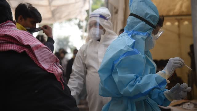 incoming travelers in queue to give their swab sample to test for coronavirus infection as health worker wearing protective gear collecting swab... - medical occupation stock videos & royalty-free footage