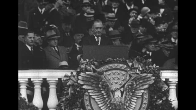stockvideo's en b-roll-footage met incoming us president franklin roosevelt speaking at his inauguration he stands behind a garlandbedecked balustrade at a podium with the great seal... - 1933