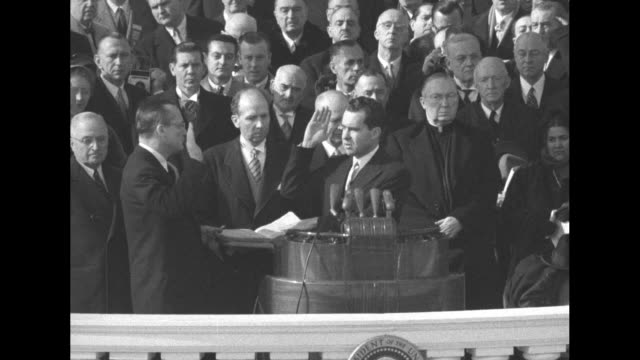 incoming vice president richard nixon with right hand raised standing at podium on east portico of us capitol takes oath of office administered by... - herbert hoover us president stock videos & royalty-free footage