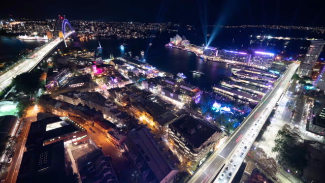 incredible introduction setup aerial of vivid sydney showing the transformation from daytime to night as the city is lit up with the vibrant colors... - fast motion tidsförlopp bildbanksvideor och videomaterial från bakom kulisserna