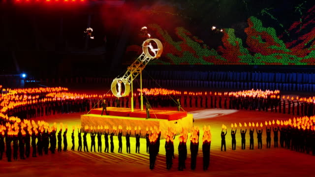 Incredible Wheel of Death perfomance. Synchronized crowd with torches moving around them during Mass Games in Pyongyang, North Korea, DPRK. Medium shot