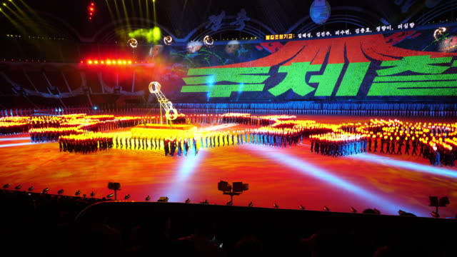incredible wheel of death perfomance. synchronized crowd with torches moving around them during mass games in pyongyang, north korea, dprk. wide shot - north korea stock videos & royalty-free footage