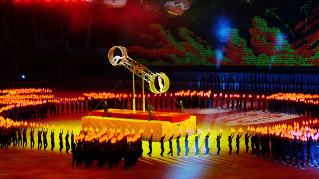 tl incredible wheel of death perfomance synchronized crowd with torches moving around them during mass games in pyongyang north korea dprk medium shot - spoonfilm stock videos and b-roll footage