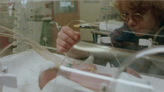 1982 montage incubated newborns in neonatal unit feeding on processed breast milk at john radcliffe hospital / oxford, oxfordshire, england - 胴体点の映像素材/bロール