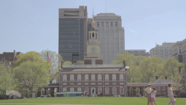 la independence hall against skyscrapers, with park and pedestrians / philadelphia, pennsylvania, united states - independence hall stock videos and b-roll footage
