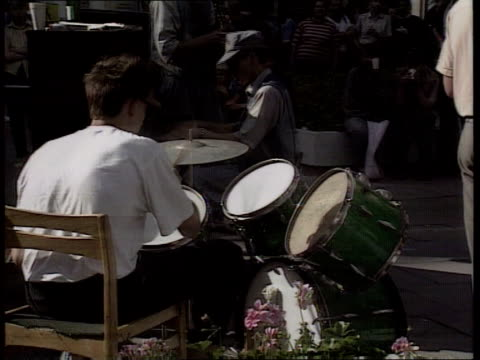 vilnius bv drummer in band playing drums bv band playing in street cms three women sitting listening ms side man standing playing trumpet - lithuania stock videos & royalty-free footage